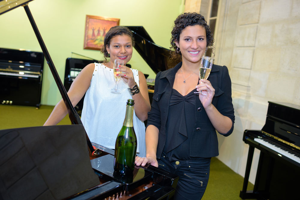 Two ladies enjoying a wine while playing piano